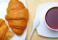 杯热的茶和新月形面包 库存照片