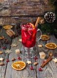 杯热的被仔细考虑的酒与成份的新年烹调,坚果和圣诞节装饰的 库存照片