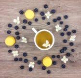 杯热的绿茶、花和莓果在木桌上 平的位置 免版税库存图片