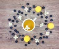 杯热的绿茶、花和莓果在木桌上 平的位置 库存图片