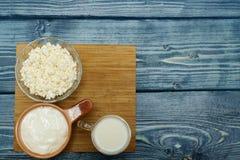 杯牛奶、酸性稀奶油和酸奶干酪在桌上 免版税库存照片