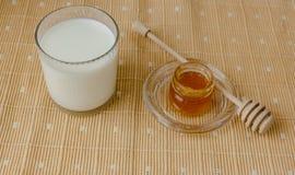 杯牛奶和瓶子在纺织品桌布的蜂蜜 免版税库存照片