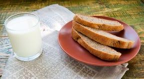 杯牛奶用在黏土板材的切好的家制面包 免版税图库摄影
