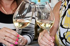杯特写镜头视图冷的酒在坐在夏天咖啡馆的桌上的妇女的手上 免版税库存照片