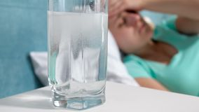 杯特写镜头4k英尺长度与溶化的阿斯匹灵药剂的水在反对遭受的妇女的床头柜上 影视素材