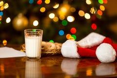 杯特写镜头牛奶和曲奇饼圣诞老人的在桌上 库存图片