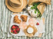 杯玫瑰酒红色,草莓,新月形面包,咸味干乳酪乳酪平位置  免版税图库摄影