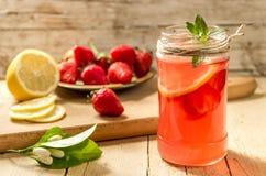 杯生气勃勃柠檬水用草莓和薄菏 免版税图库摄影
