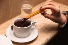 杯用举行churros的女孩的热巧克力和手 图库摄影