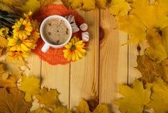 杯用咖啡和甜点在桌上在秋叶框架  免版税库存图片