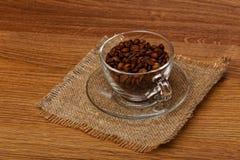 杯用在布料粗麻布的咖啡豆 免版税图库摄影