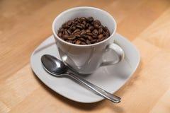 杯用在茶碟的咖啡豆填装了 库存照片
