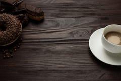 杯用在黑暗的木背景的咖啡和巧克力多福饼 免版税库存照片