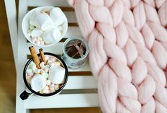 杯用热巧克力,碗用蛋白软糖,瓶子用巧克力,桃红色淡色巨型格子花呢披肩 库存图片