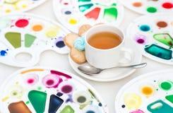 杯用茶和曲奇饼围拢了水彩调色板 图库摄影