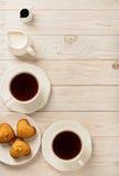 杯用茶和杯形蛋糕以心脏的形式在光wo 免版税库存图片
