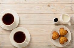 杯用茶和杯形蛋糕以心脏的形式在光wo 免版税图库摄影