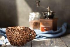 杯由咖啡豆制成,站立在灰色木桌 免版税图库摄影