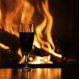 杯由壁炉的红色香槟 库存图片