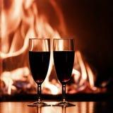 杯由壁炉的红色香槟 免版税库存图片