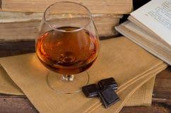 杯白兰地酒和巧克力在木桌上与书 免版税库存照片