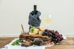 杯白葡萄酒、乳酪板、葡萄、无花果、草莓、蜂蜜和面包条在土气木桌,光上 免版税图库摄影