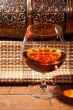 杯科涅克白兰地用在木背景的柠檬 库存图片