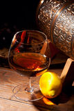 杯科涅克白兰地用在木背景的柠檬 图库摄影