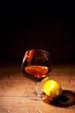 杯科涅克白兰地用在木背景的柠檬 库存照片