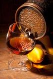 杯科涅克白兰地用在木背景的柠檬 免版税图库摄影