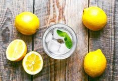 杯简单的苏打用在木桌上的柠檬 库存照片