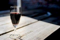杯红色口岸,在木桌上 库存照片