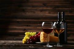 杯红色和白葡萄酒、乳酪和葡萄在棕色木背景 免版税图库摄影