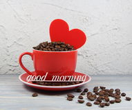 杯红色用咖啡粒、心脏和一题字早晨好 免版税库存图片
