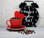 杯红色用咖啡粒、心脏和闹钟 库存照片