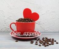 杯红色以咖啡粒、心脏和题字好的妙语胃口 免版税库存图片