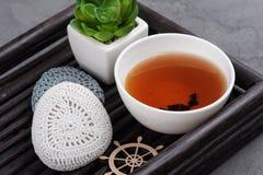 杯红茶和钩针编织的小卵石 免版税图库摄影