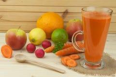 杯红萝卜汁和红萝卜在木桌上 充分健康汁液维生素和纤维 饮食食物 免版税库存图片