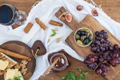 杯红葡萄酒、乳酪板、葡萄、核桃、橄榄、蜂蜜和面包条 免版税库存照片