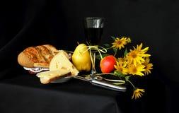 杯红葡萄酒、家制面包、乳酪和花 免版税库存图片