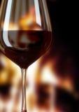 杯红葡萄酒和火地方 库存图片
