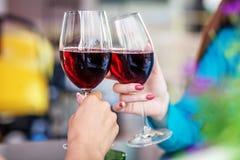 杯红葡萄酒在他们的手上 敬酒党的概念 库存图片