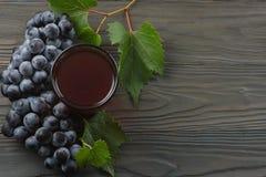 杯红葡萄酒用蓝色葡萄和绿色叶子在黑暗的木桌上 与拷贝空间的顶视图 免版税库存图片