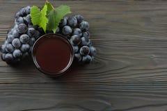 杯红葡萄酒用蓝色葡萄和绿色叶子在黑暗的木桌上 与拷贝空间的顶视图 库存图片