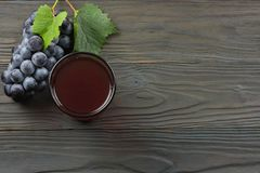 杯红葡萄酒用蓝色葡萄和绿色叶子在黑暗的木桌上 与拷贝空间的顶视图 库存照片