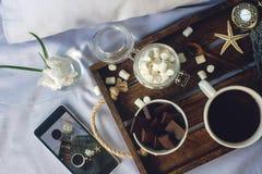 杯自创可可粉用蛋白软糖、巧克力、花和智能手机在土气木盘子在舒适床上 免版税库存照片