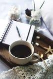 杯自创可可粉用蛋白软糖、巧克力、花和智能手机在土气木盘子在舒适床上 库存照片