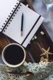 杯自创可可粉用蛋白软糖、巧克力、花和智能手机在土气木盘子在舒适床上 免版税库存图片