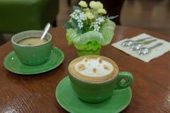 杯艺术在书桌(在第一个杯子和Bac的焦点上的热奶咖啡咖啡 免版税图库摄影