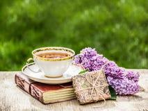 杯芬芳茶、新鲜的丁香和礼物 浪漫概念 概念季节性分隔的白色 庭院茶 库存照片